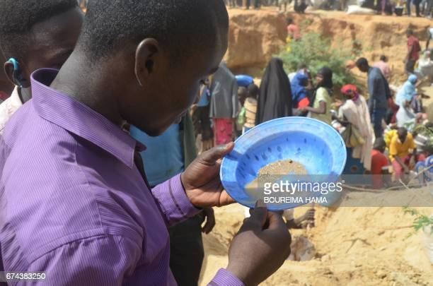 A man looks in a sieve as hundreds of people search gold on April 25 2017 in KafaKoira south of Niamey Hundreds of people sometimes whole families...