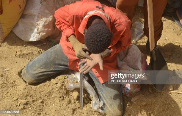 A man looks in his hand as hundreds of people search gold on April 25 2017 in KafaKoira south of Niamey Hundreds of people sometimes whole families...