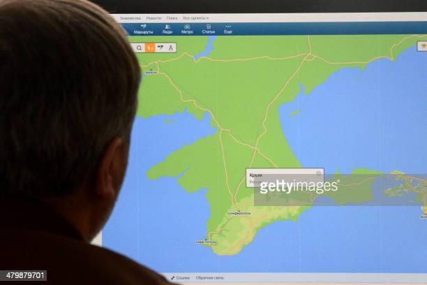 A man looks in Moscow on March 21 at a computer screen displaying a map of Crimean peninsula with a popup window reading 'Crimea Russia' at the site...