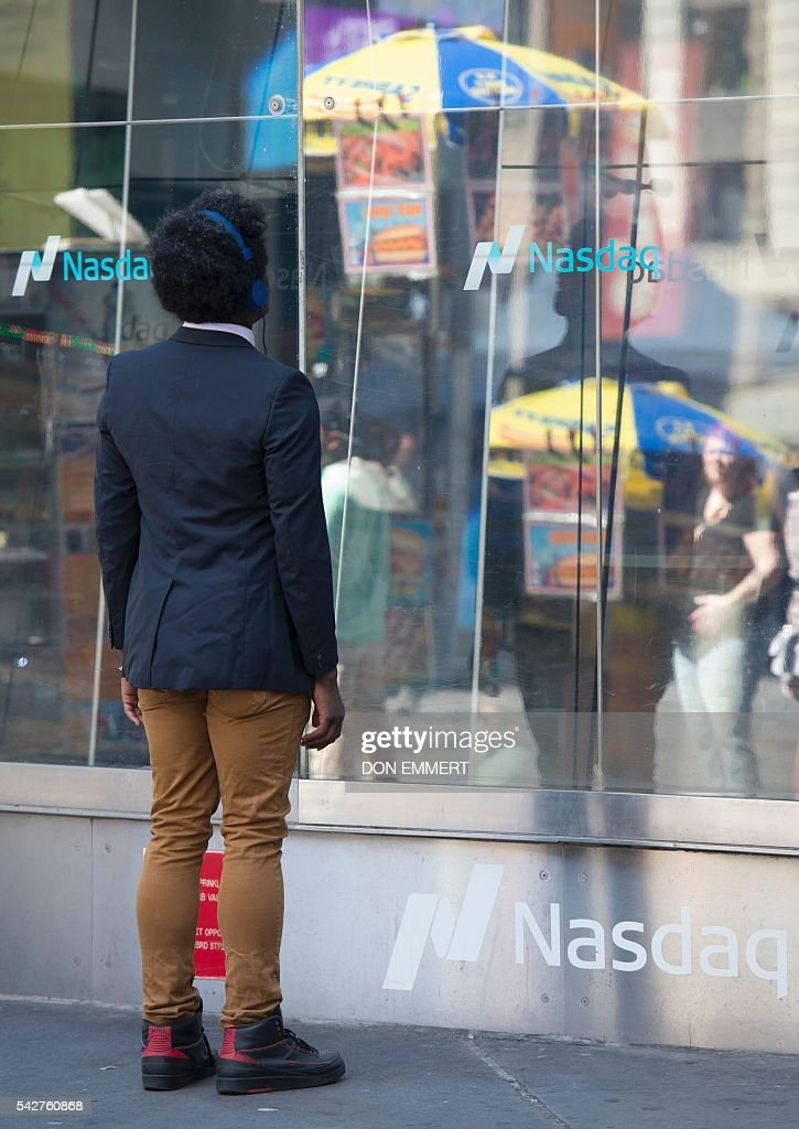 A man looks in the window at the Nasdaq offices in Times Square on June 24, 2016 in New York. US stocks tumbled early Friday, with banking equities suffering especially deep losses, joining an international rout after Britain's surprise vote to exit the European Union. The Dow sank more than 500 points shortly after the markets opened at 1330 GMT, but then quickly recovered some of the losses. The selloffs in the US were smaller than in many overseas markets. EMMERT