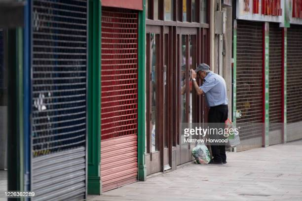 Man looks in the window of a closed coffee shop during the coronavirus lockdown period on May 21, 2020 in Cardiff, United Kingdom. The British...