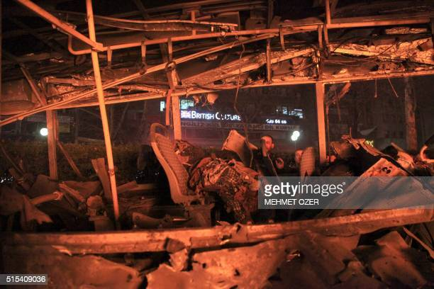 TOPSHOT A man looks into a burntout bus at the site of a blast in Ankara on March 13 2016 A suicide car bomb ripped through a busy square in central...