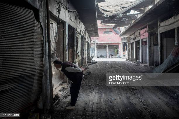 A man looks into a destroyed shop in an outer neighborhood of the Old City in West Mosul on November 6 2017 in Mosul Iraq Five months after Mosul...