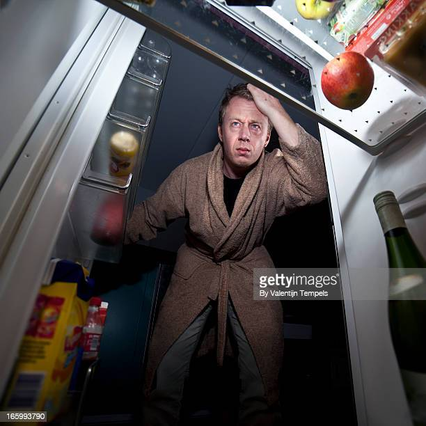man looks into fridge - frigo humour photos et images de collection
