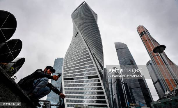 Man looks into his smartphone sitting in front of the towers of Moscow's International Business Centre in Moscow on August 13, 2020.