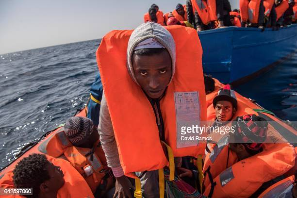 Man looks into the camera as migrants and refugees are assisted by members of the Spanish NGO Proactiva Open Arms as they crowd on board of a wooden...