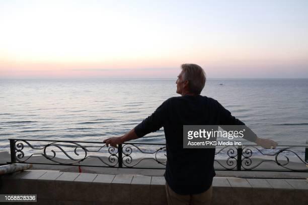 man looks off across sea from terrace - garde corps photos et images de collection