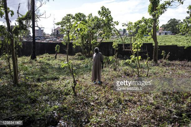Man looks on after helping to clean the famous Bambeto Cemetery in Conakry on September 18 as the Bambeto cemetery is where most opposition...