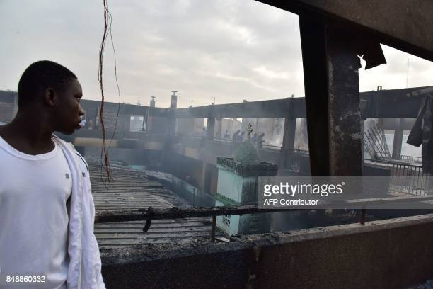 A man looks on amid debris in the market after a fire devastated the building during the night on September 18 2017 in Abobo neighborhood of Abidjan...