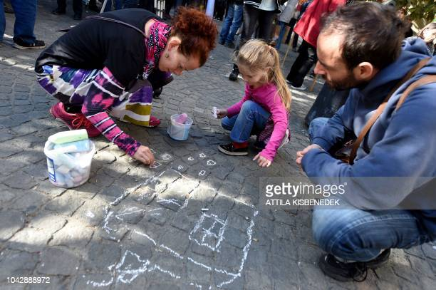A man looks on as a woman and a child draw with chalk a house on the pavement on the sidelines of a demonstration against the Hungarian government's...