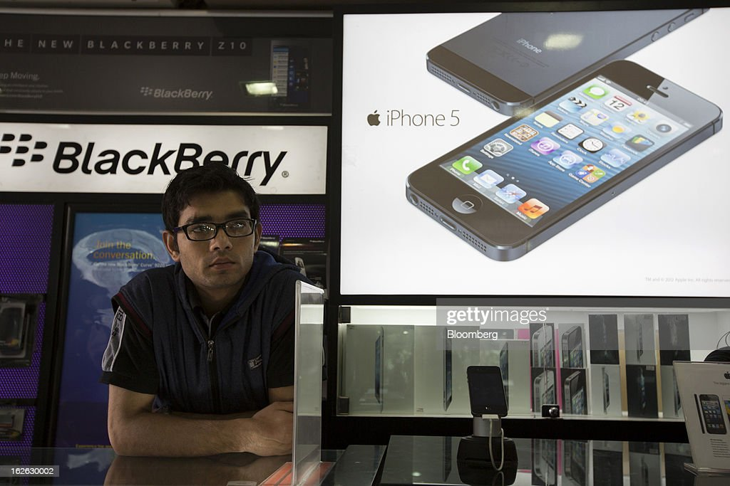 A man looks on as an Apple Inc. iPhone 5 advertisement, right, and a Blackberry Z10 advertisement, rear left, are displayed in store in Connaught Place in New Delhi, India, on Saturday, Feb. 23, 2013. Finance Minister Palaniappan Chidambaram, who will present his annual budget to parliament on Feb. 28, will seek to narrow the shortfall to 4.8 percent of gross domestic product in the year starting April, from this year's goal of 5.3 percent, according to a Bloomberg survey of analysts and investors. Photographer: Brent Lewin/Bloomberg via Getty Images