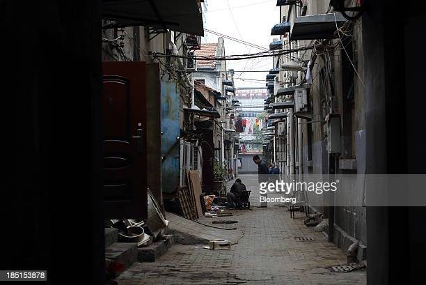 A man looks on as another works in an alley between houses in Wuhan China on Thursday Oct 17 2013 China is scheduled to release thirdquarter gross...