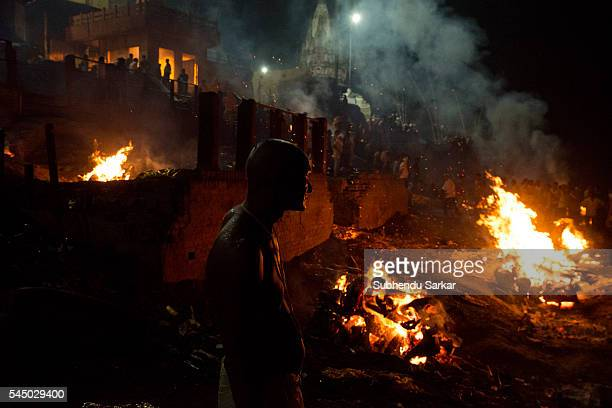 A man looks on as corpses are being cremated at night at Manikarnika ghat in Varanasi It is a traditional holy place on the banks of river Ganges to...