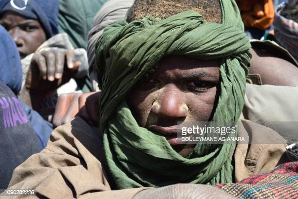 TOPSHOT A man looks on as he sits in the back of a pick up with other migrants mainly from Niger and Nigeria on January 22 during a journey across...