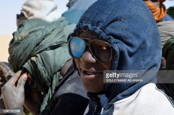 A man looks on as he sits in the back of a pick up with other migrants mainly from Niger and Nigeria on January 22 during a journey across the Air...