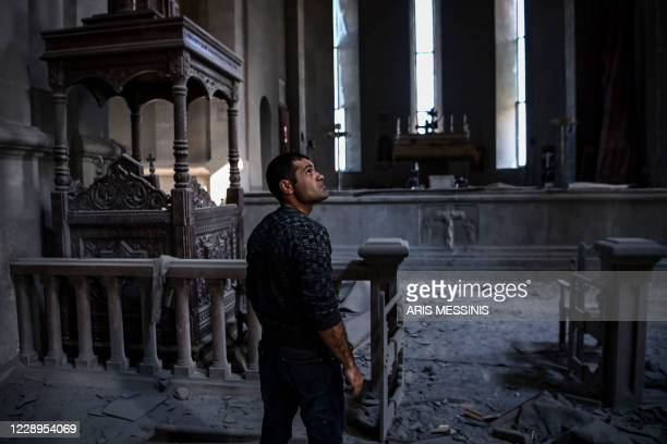 Man looks on as he stands in the rubble and debris on October 8, 2020 inside the damaged Ghazanchetsots Cathedral in the historic city of Shusha,...