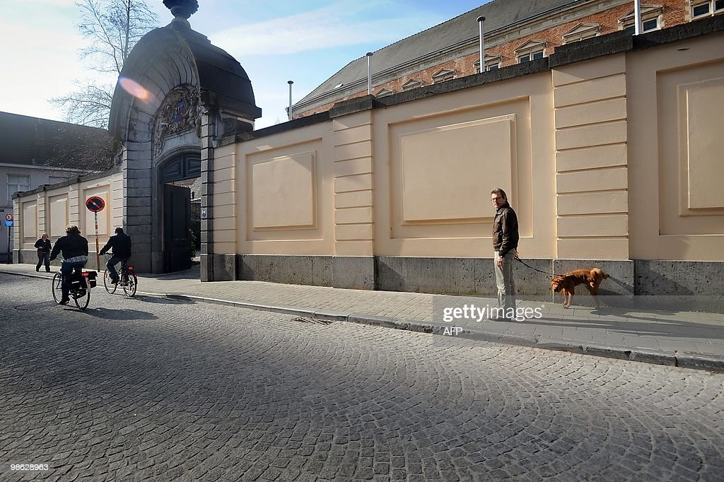 A man looks on as his dog urinates on th : Nieuwsfoto's