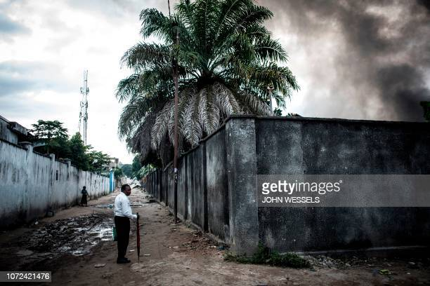 TOPSHOT A man looks on as smoke rises from a fire at the independent national electoral commission's warehouse on December 13 2018 in Kinshasa ten...