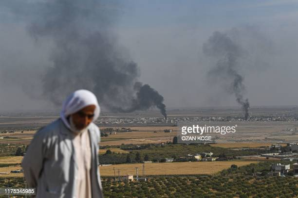 Man looks on as smoke rises from the Syrian town of Ras al-Ain, in a picture taken from the Turkish side of the border in Ceylanpinar on October 11...