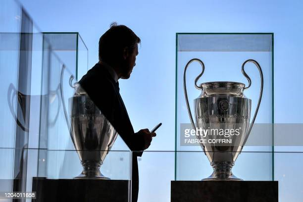 A man looks on as the UEFA Champions League trophy is displayed at the UEFA headquarters on February 28 2020 in Nyon