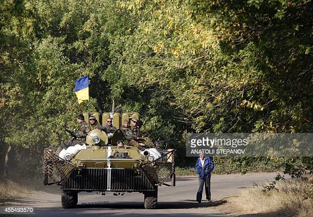 A man looks on as Ukrainian servicemen sitting atop of an Armoured Personnel Carrier drive past during a patrol in Donetsk region on September 15...