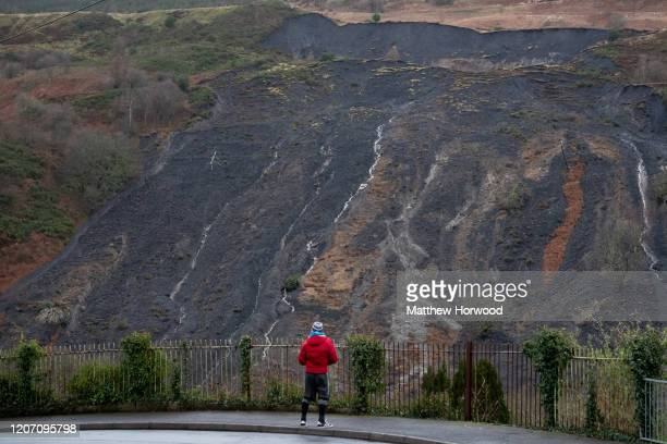 A man looks on at a landslide in the Rhondda valley on February 18 in Tylorstown Wales Inspections of old coal tips on the mountains in the Rhondda...