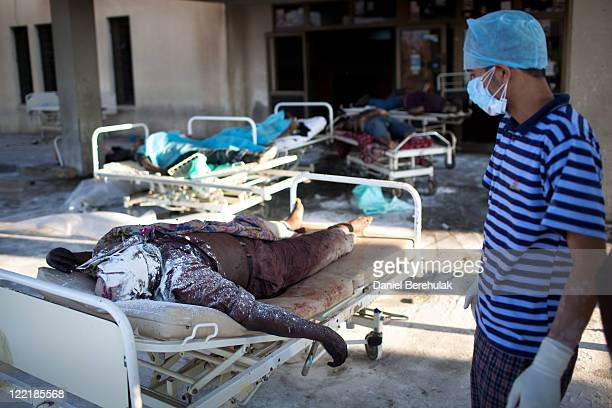 A man looks on at decomposing bodies of proGaddafi loyalist soldiers at the Abu Salim Hospital on August 26 2011 in Tripoli Libya Heavy fighting...