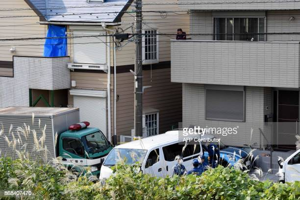 A man looks on at policemen gathering in front of an apartment where Japanese police found nine bodies including two with their heads severed and...