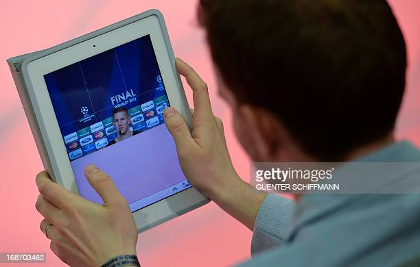 Man looks on his tablet computer displaying a picture of Bayern Munich's midfielder Bastian Schweinsteiger during a press conference at the FC Bayern...