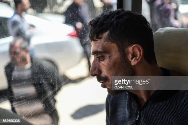 TOPSHOT A man looks on in a bus carrying Syrian victims of suspected chemical attack back to the Syrian border after treatment at Reyhanli hospital...