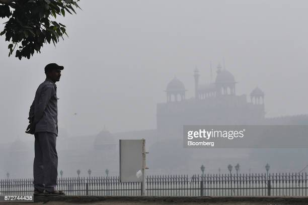 A man looks on in front of a building shrouded in smog in New Delhi India on Saturday Nov 11 2017 Thick toxic smog enveloped New Delhi forcing...