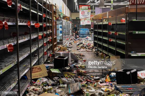 A man looks on inside a looted supermarket on November 28 2019 in Santiago Chile Violent protests looting and arson occurred yesterday in Chile...