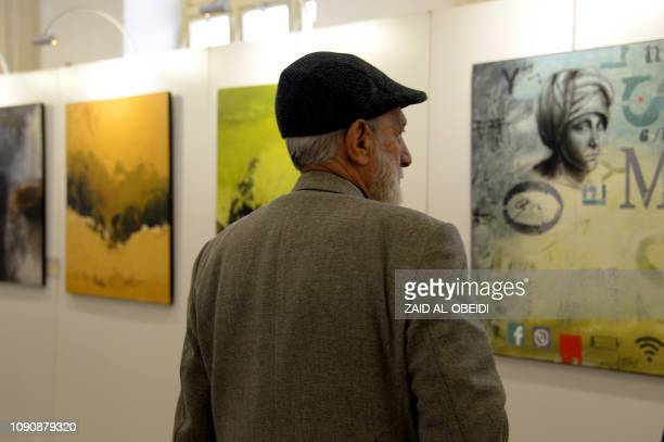 A man looks on January 29 2019 at paintings displayed at a contemporary art exhibition hall in the museum of the northern Iraqi city of Mosul which...