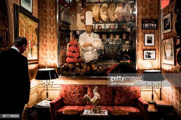 A man looks on next to a portrait of French chef Paul Bocuse in the Bocuse restaurant 'L'auberge du Pont de Collonges' on January 20 2018 in...