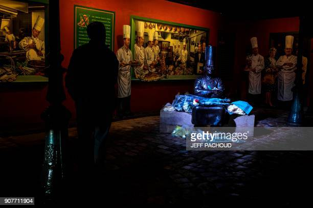 A man looks on next to the statue of French chef Paul Bocuse in the courtyard of his restaurant 'L'auberge du Pont de Collonges' on January 20 2018...