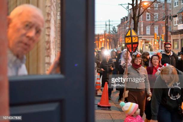 A man looks on through the galls of a front door as hundreds participate in the eight annual Parade of Spirits Krampus Parade through the Northern...