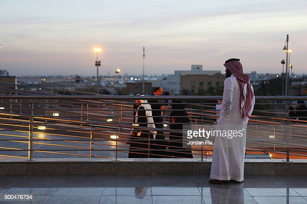 A man looks on while others arrive to participate at the first annual ' Bab Rizq Jameel' a job opportunity fair for Saudi youth that is taking place...