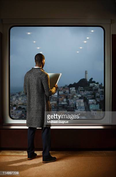 A man looks out a window overlooking a city.