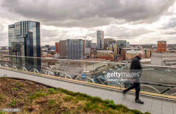 Man looks out across Centenary Square from the roof of the Library of Birmingham in Birmingham city centre on March 20, 2020 in Birmingham, England.