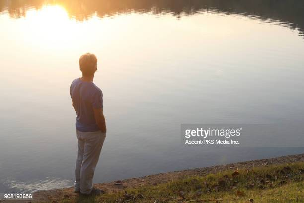 Man looks out across lake, at sunrise