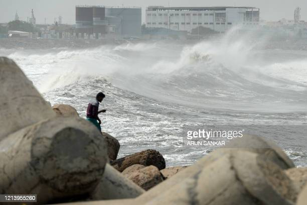 A man looks out as waves hit a breakwater at Kasimedu fishing harbour in Chennai on May 19 as Cyclone Amphan barrels towards India's eastern coast...