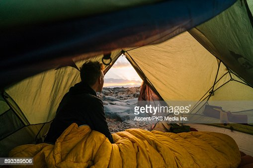 Man looks out at sunset from sleeping bag inside tent