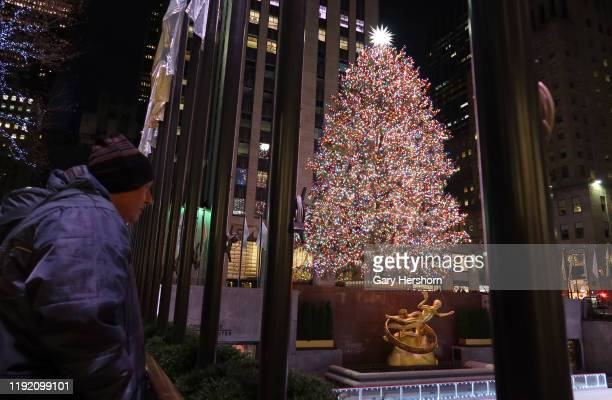 Man looks out at the Christmas tree in Rockefeller Center before sunrise on December 5 in New York City.