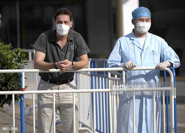 A US man looks out beside a Chinese medic in a courtyard of the Yan Xiang Hotel where a group of tourists are being quarantined by Chinese...