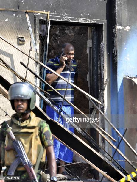 A man looks out from a burnt out home as a Sri Lankan police commando patrols on the streets of Pallekele a suburb of Kandy on March 6 following...