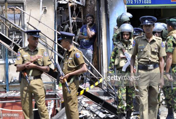 A man looks out from a burnt out home as Sri Lankan police commandos patrol on the streets of Pallekele a suburb of Kandy on March 6 following...