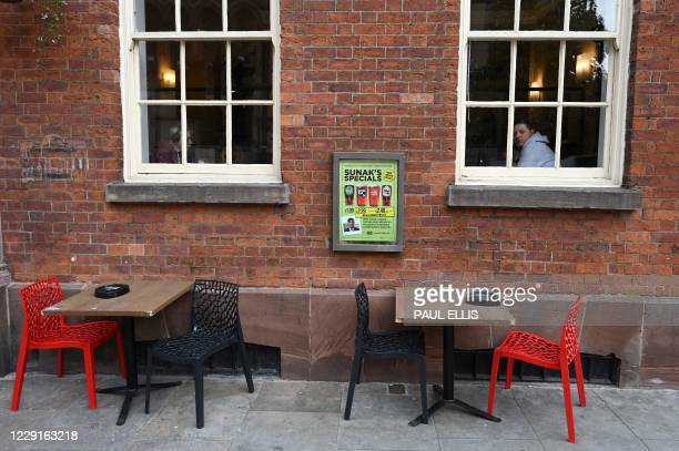 Man looks out from a pub window in Manchester, northwest England as the country battles a surge in coronavirus cases on October 19, 2020