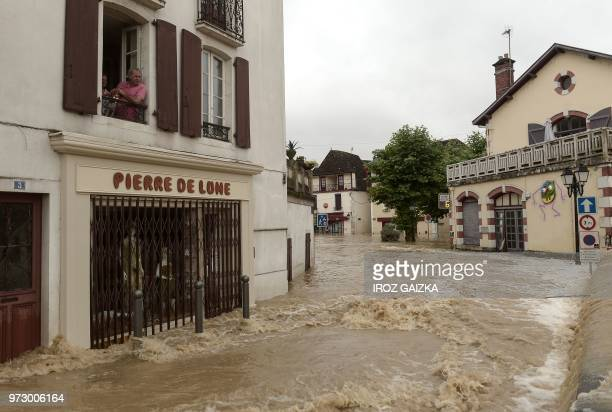 A man looks out of a first floor window watching flood waters sweep through the streets following heavy rains in SaliesdeBearn south western France...