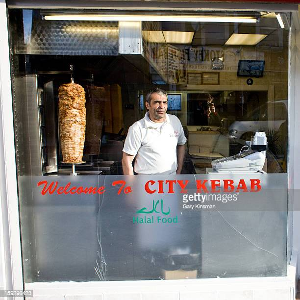 Man looks out of the window of the City Kebab restaurant in Stoke Newington, London