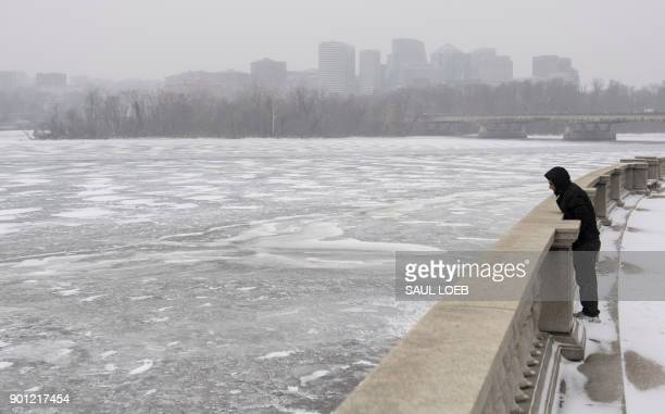 A man looks out over a frozen Potomac River during a snow storm in Washington DC January 4 2018 A giant winter bomb cyclone walloped the US East...